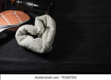 Sneakers, bottle and a towel stylized to the heart on the floor of gym .  Top view. Space for text.