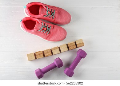 Sneakers, cubes with space for text and dumbbells on wooden background