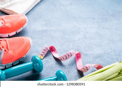 Sneakers and dumbbells fitness over blue background. Different tools for sport. Sport shoes and water with set for sports activities on floor, top view.