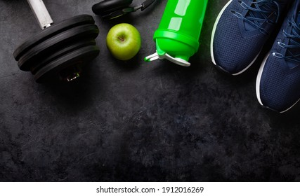 Sneakers, food and dumbbells. Sport, fitness and healthy lifestyle background. Top view flat lay with copy space