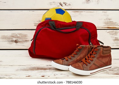 Sneakers, gym bag and ball in a locker room. Sport and football game. Physical education classes concept.