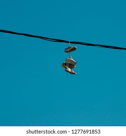 Sneakers hanging on a sky background. The concept of urban kultruta, sale of prohibited substances, ghetto