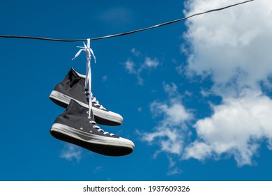Sneakers hanging on wires against the blue sky.