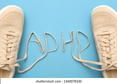 Sneakers with laces in adhd abbreviation text. Flat lay on blue background. Attention deficit hyperactivity disorder concept