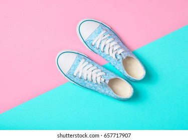 Sneakers lie on a multi-colored pastel surface. Top view. Fashion 90s