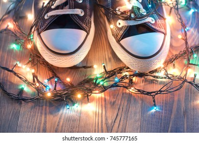 Sneakers like keds surrounded by New Year's lights on a rustic wooden background, Christmas present to an athlete