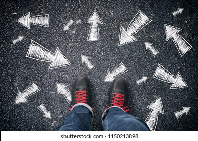 Sneakers on the asphalt road with drawn arrows pointing in many different directions. Making decisions and making choices concept.