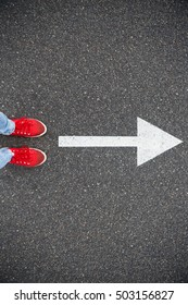 Sneakers on the asphalt road with drawn direction arrow