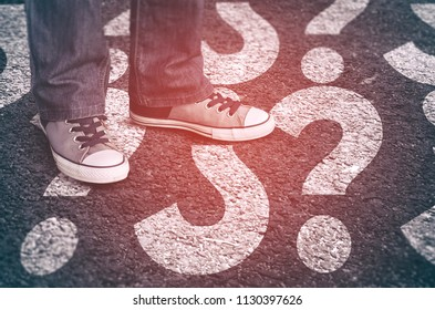 Sneakers on asphalt road with painted question mark signs. Dilemmas concept.