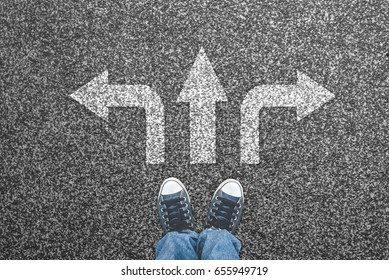 Sneakers on the asphalt road with three arrows pointing. Making decisions concept