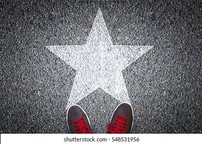 Sneakers on asphalt road with white star shape