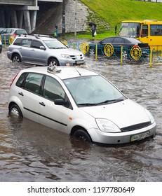 Sneakers on car roof, traffic on flooded city road, Kiev, Ukraine