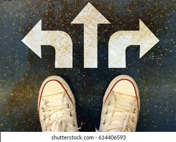 Sneakers shoes with three white arrows print pointing on grunge road , making decision business concept