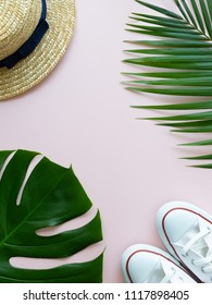 Sneakers, tropical leaves and summer hat on the pink background. Minimal summer concept. Hipster vibes