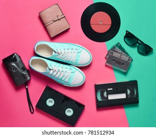 Sneakers, vinyl records, audio cassettes, video cassettes, plastic vintage camera, purse are laid out on a neon colored surface. Entertainment 90s. Top view. Flat lay.