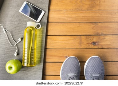 Sneakers, water, apple, smartphone, earphones and yoga mat