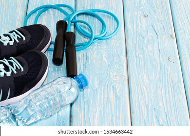 sneakers water bottle, and jump rope on light blue wooden background