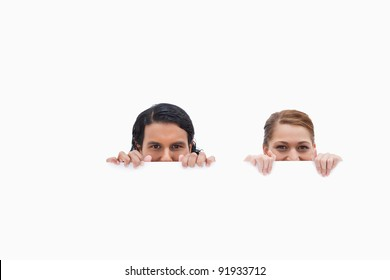 Sneaky couple looking over blank wall against a white background