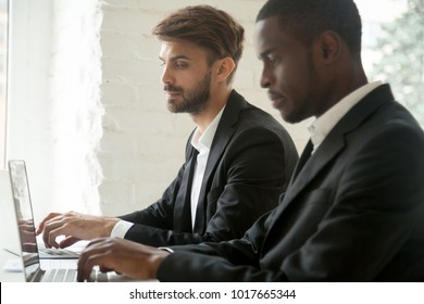 Sneaky curious caucasian businessman secretly looking at laptop screen of african colleague stealing idea, white office corporate spy in suit copying work of black coworker, rivalry at workplace