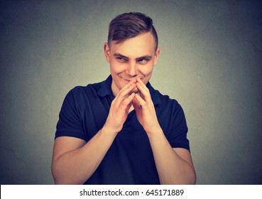 Sneaky man plotting something isolated on gray wall background. Negative human emotion facial expression feeling attitude