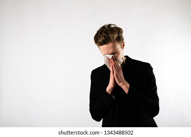 Sneeze. Young man in black is sneezing. Allergy concept.