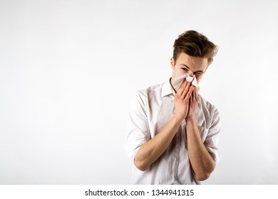 Sneeze. Young man in white is sneezing. Allergy concept.