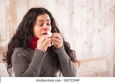 Sneezing beauty. Young sick woman with scarf on her neck sitting in bed and sneezing with her country house on the background