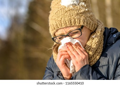 Sneezing woman blowing her nose with a tissue. Sick woman with cold and flu in winter, outdoors. Girl in warm clothes - hat and scarf