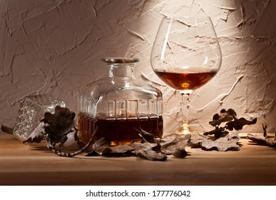 snifter with brandy and dried oak leaves