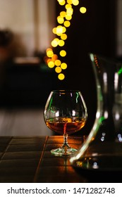 Snifter of brandy in elegant glass with space for text on dark colorful background. Decanter defocussed. Traditional French drink. Stiff drink. Service and tasting concept.