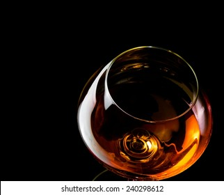 snifter of brandy in elegant glass with space for text on black background