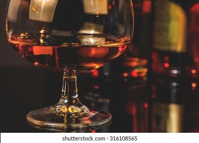 snifter of brandy in elegant typical cognac glass  in front of bottles in background, warm atmosphere