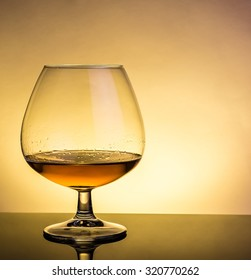 snifter of brandy in elegant typical cognac glass on table with reflection on warm atmosphere