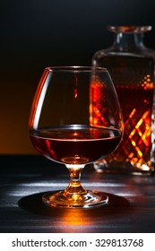 Snifter with brandy on black wooden table