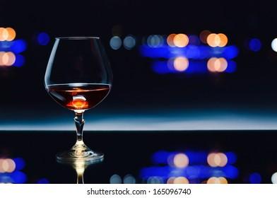 snifter with brandy on  dark background
