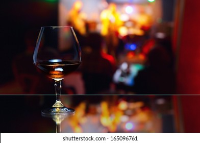 snifter with brandy on glass table in nightclub