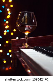 snifter with brandy on old piano in bar