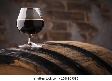 Snifter glass with black stout beer standing on an oak barrel in a cellar