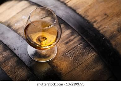 Snifter glass of brandy standing on an oak barrel in a cellar