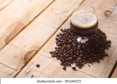 Snifter glass with coffee stout surrounded by roasted coffee beans over a grunge wooden background