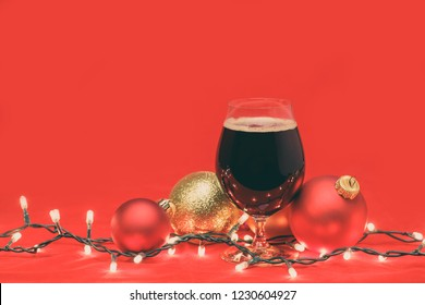 Snifter glass of dark ale or porter beer with  christmas lights and baubles on red background