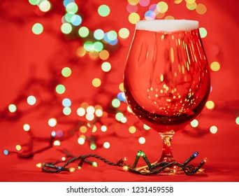 Snifter glass of pale lager beer or ale with  christmas lights on red background