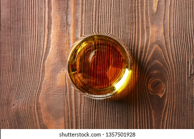 Snifter glass with pure whiskey on wooden table