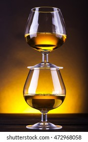 Snifter glasses with brandy stacked on top of each other over a yellow lit background
