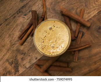 A snifter of stout beer with cinnamon sticks on a wood table