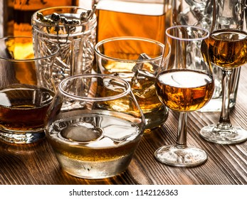 Snifters, old fashined glasses filled with whiskey on a bar top