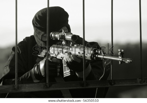Sniper in a camouflage shoots from a rifle.