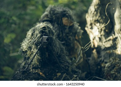 Sniper with camouflage suit in the green forest