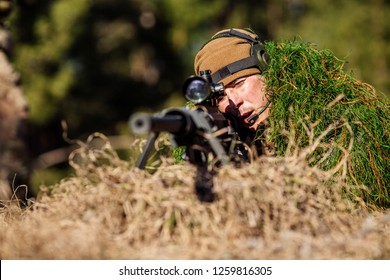 sniper laying on the ground covered in a ghille suite tall grass and trees in the background. military concept.