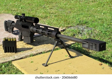 Sniper rifle .50 BMG caliber with muzzle brake. Long rifle on bipod and ammunition near is ready for shooting.